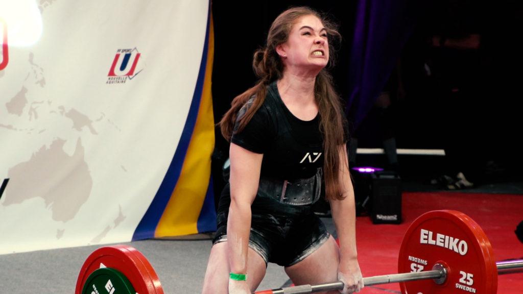 Jeune fille qui soulève une barre d'haltérophilie pendant une compétition
