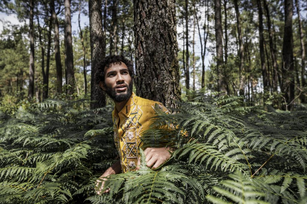 jeune homme caché dans les arbres avec une chemise jaune